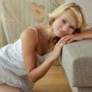 Very beautiful blonde Eve B on gray sofa