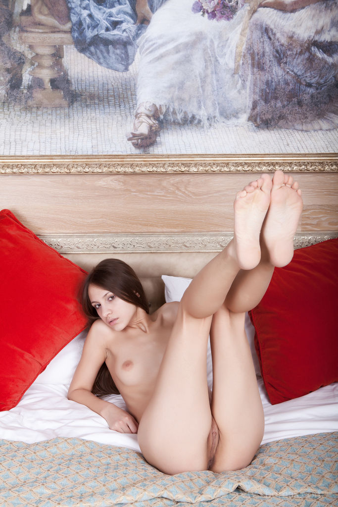 Dalida relaxes on her bed and plays with her shaved pussy