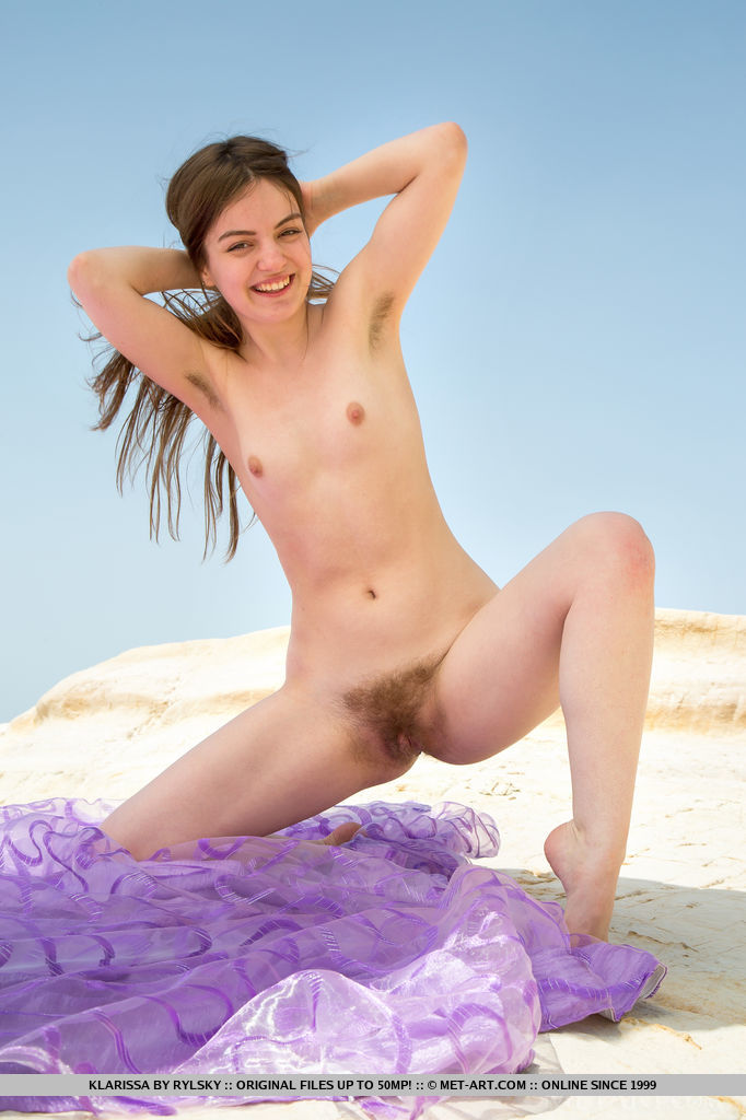 Klarissa playfully poses outdoors as she bares her unshaven pussy.