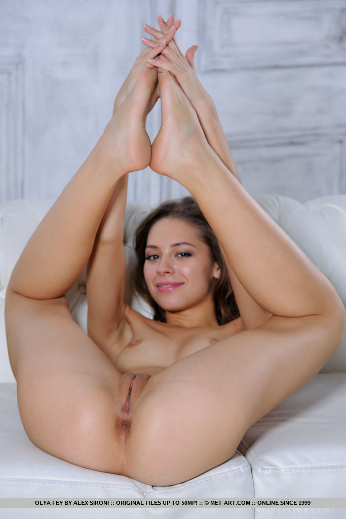 Olya Fey sensually poses on the sofa as she displays her sweet pussy.