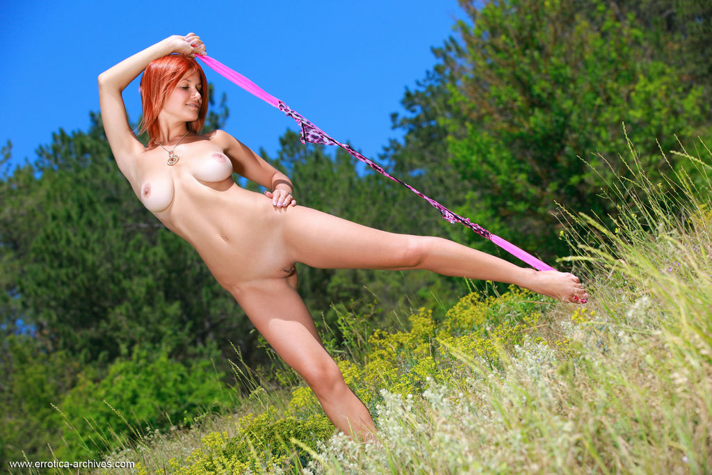 Redhead Violla A strips on the flower field as she bares her gorgeous body.