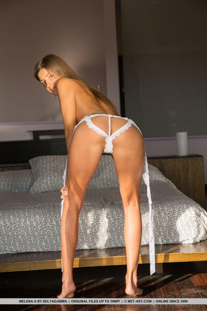 Top model Melena A strisp her sexy, white lingerie on the bed.