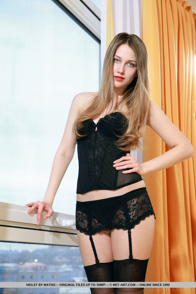 A seductive Violet confidently posing in her black bustier lace, matching lace garter belt, and black stockings