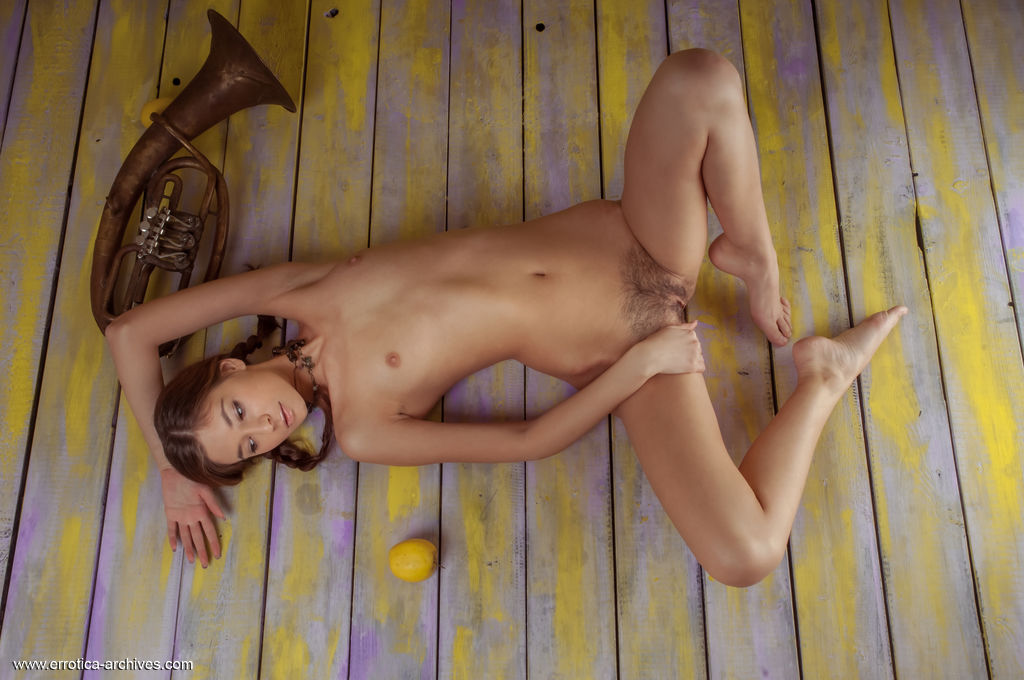 Afrodita sensually poses on the floor as she bares her hairy pussy.