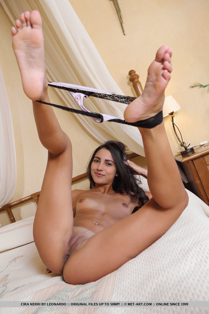 Cira Nerri strips on the bed baring her smooth pussy.