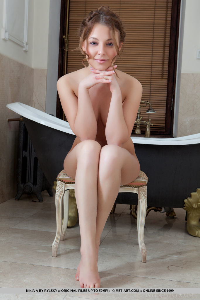 Cute and youthful Nikia A playfully posing naked by the porcelain bath tub