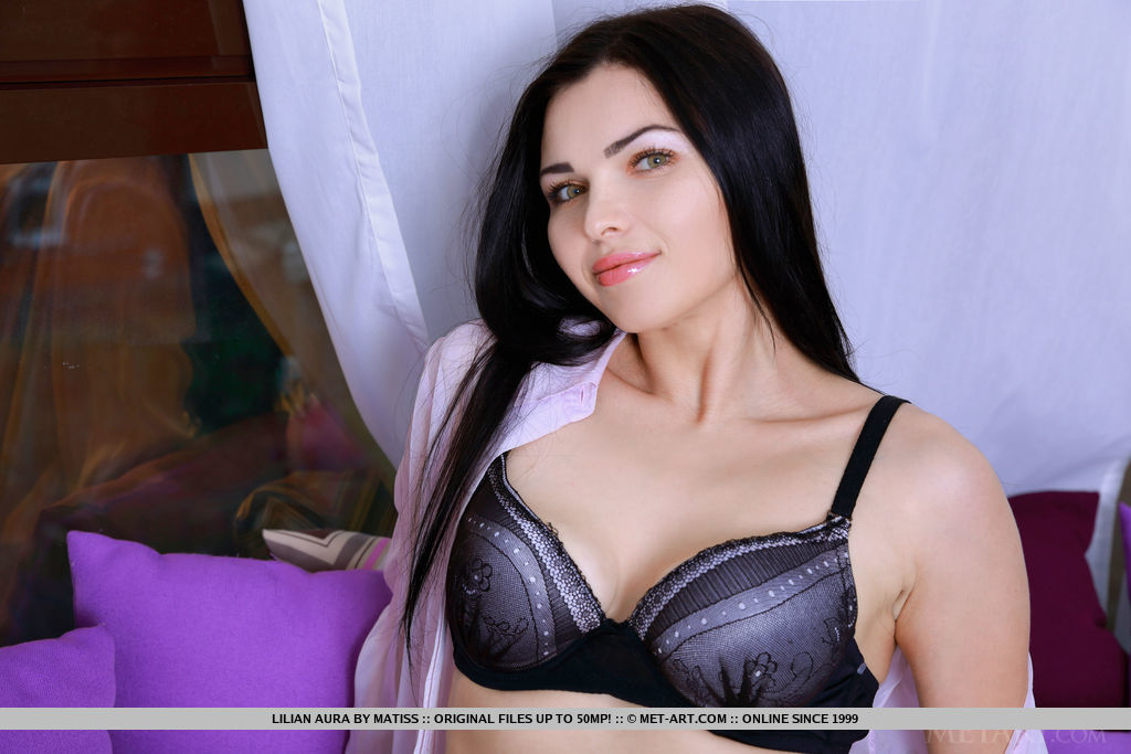 Dark-haired beauty Lillian Aura in a matching black lingerie and thigh-high stockings