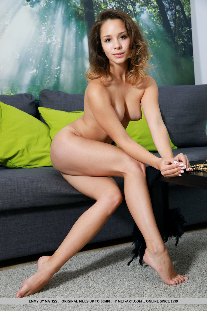 Emmy strips her sexy stockings as she poses on the couch.