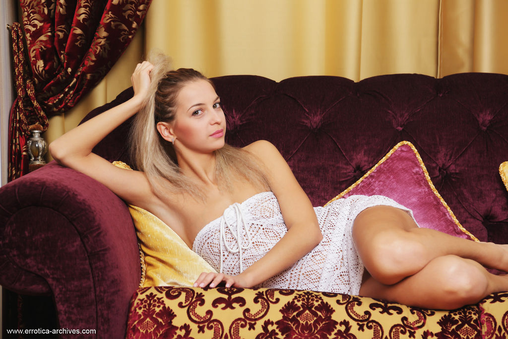 Leonie strokes her smooth, pink pussy as she relaxes on the sofa