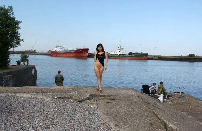 Naked russian girl walks behind fishermen