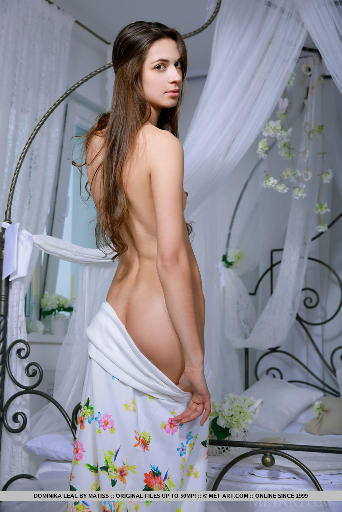 New model Dominika Leal bares her petite body on the bed.