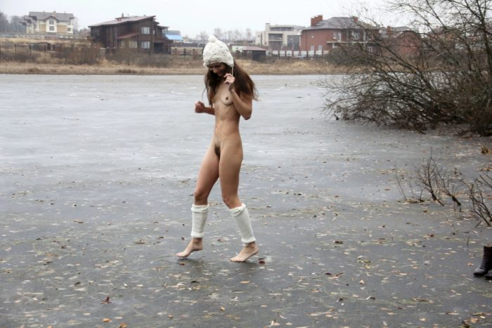 Russian teen walks on frozen lake in boots and hat