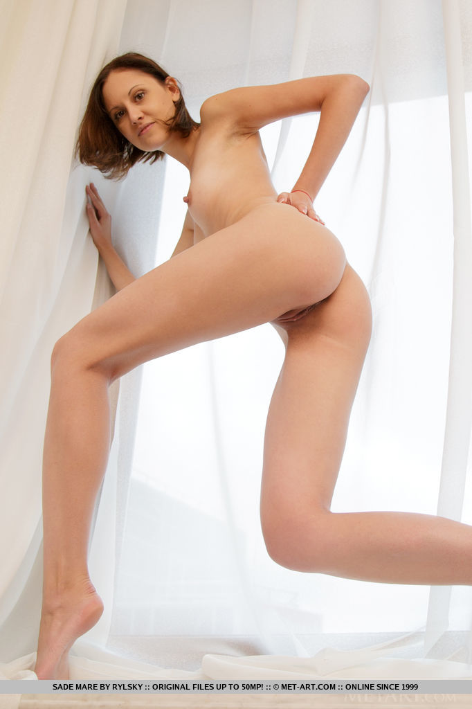 Sade Mare shows off her petite body with tight butt and sweet pussy as she poses by   the window.
