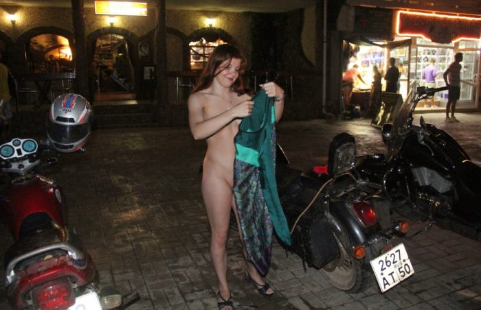 Shamelesss redhead undresses on busy night street