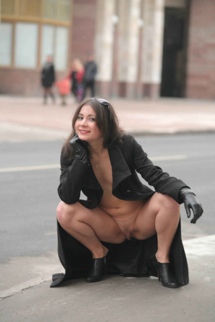 Smiling girl Nataly wears coat on bare body