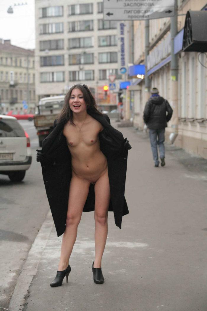 Smiling girl Nataly wears coat on bare body
