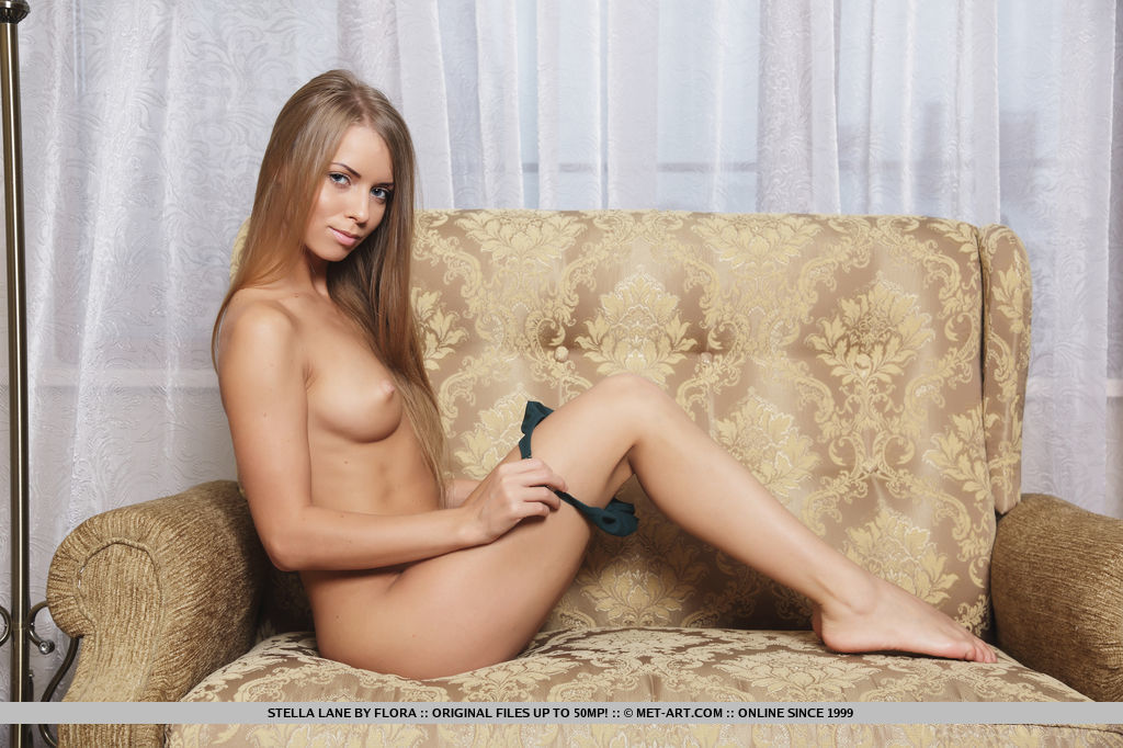 Stella Lane strips her lingerie baring her lean, tight  body with tight ass as she poses   on the couch.