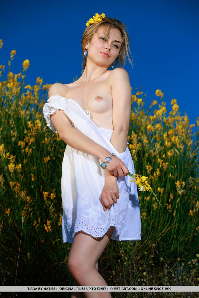 Tiara playfully poses outdoors baring her smooth, cream body.
