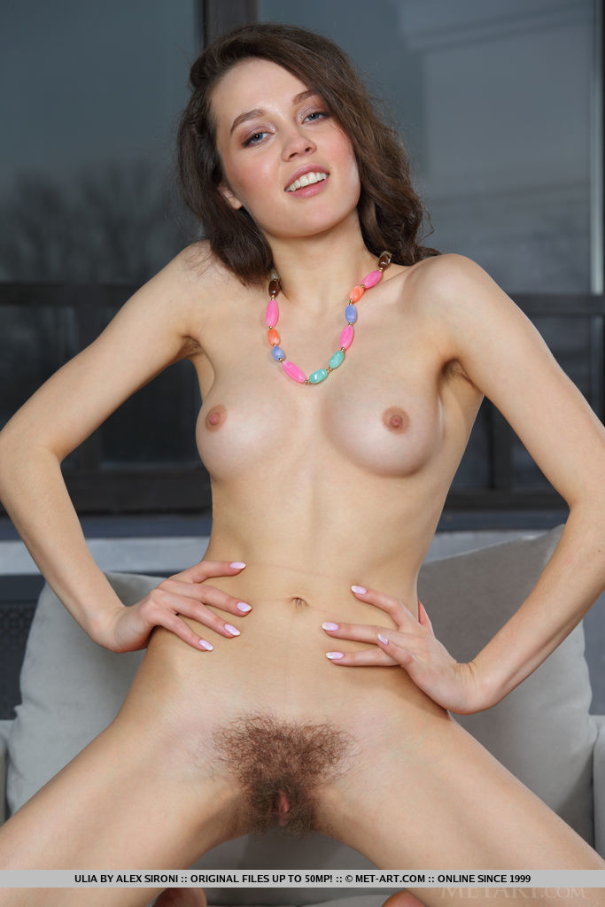 Ulia sensually poses on the couch baring her hairy pussy.