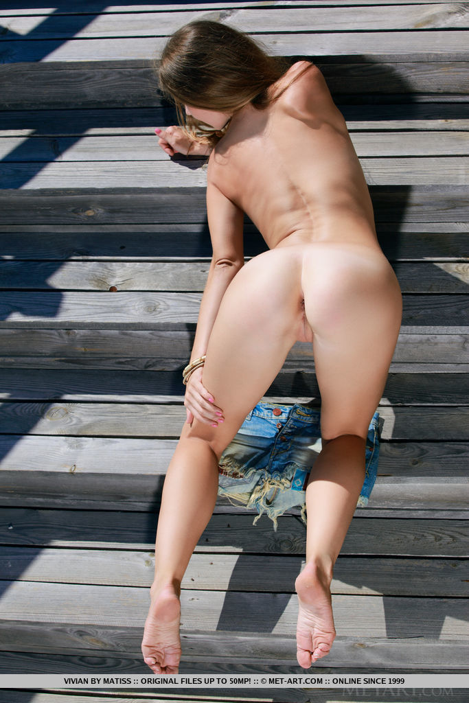 Vivian strips outdoors baring her nubile body on the chair.