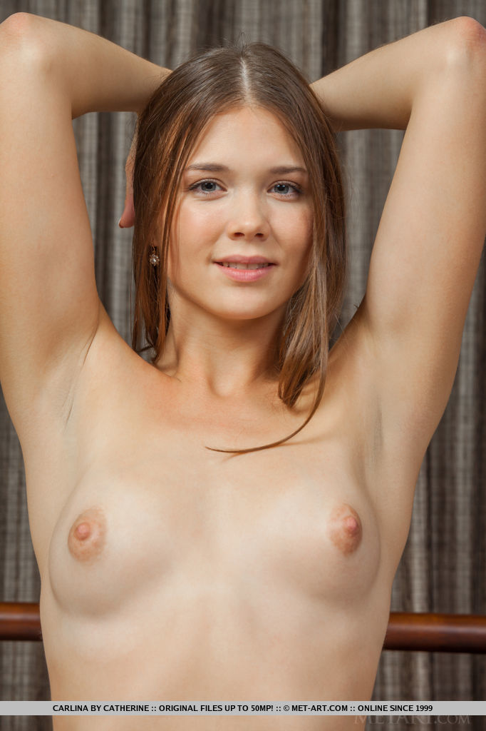 A smiling Carlina posing naked on top of the bed, spreading her legs wide open for a full view of her shaved pussy and smooth legs