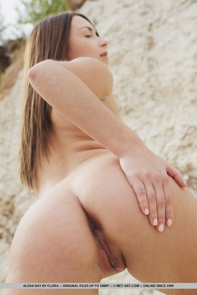 Alexa Day gets naked by the beach, her delicate physique and smooth body stands out against the rugged terrain