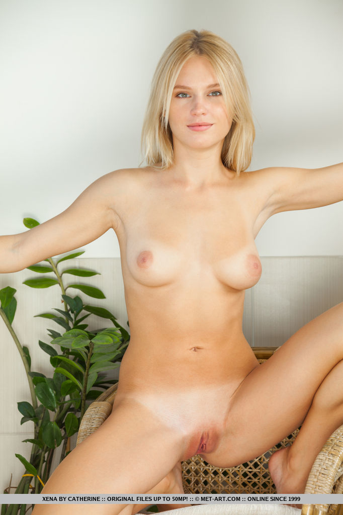 Alluring Xena shows off her lusty body and yummy pussy as she poses on the   chair.