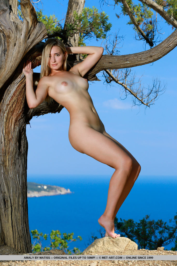 Amaly strips outdoors as she playfully poses by the tree.
