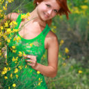 Amidst a bush of dainty flowers, redhead Violla A playfully poses, showing off her luscious body and smooth assets