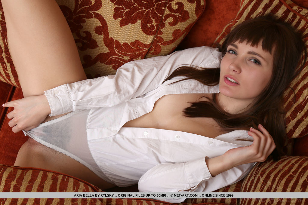 Aria Bella displays her slender body and delectable assets as she sensually poses on   the sofa.