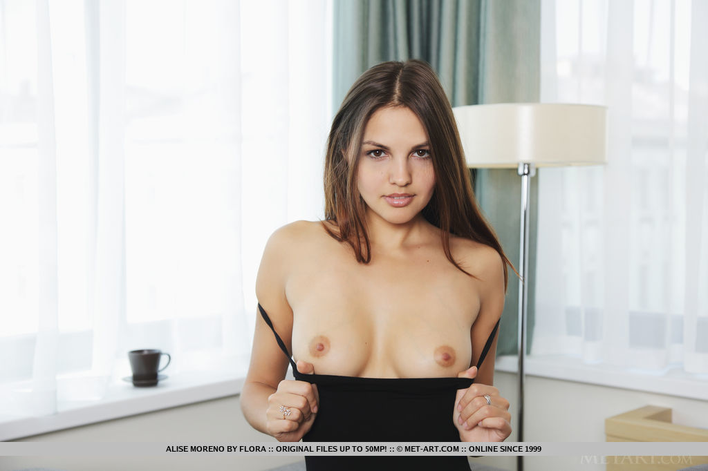 Elegant beauty Alise Moreno lounges by the sofa, enjoying her cup of coffee before indulging in a naughty striptease