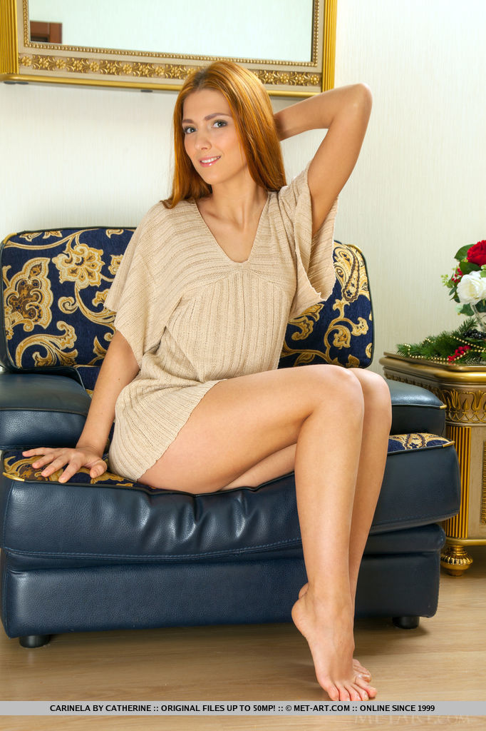 Pretty redhead Carinela lounges by the sofa, showing off her meaty ass, sexy legs, and shaved pussy