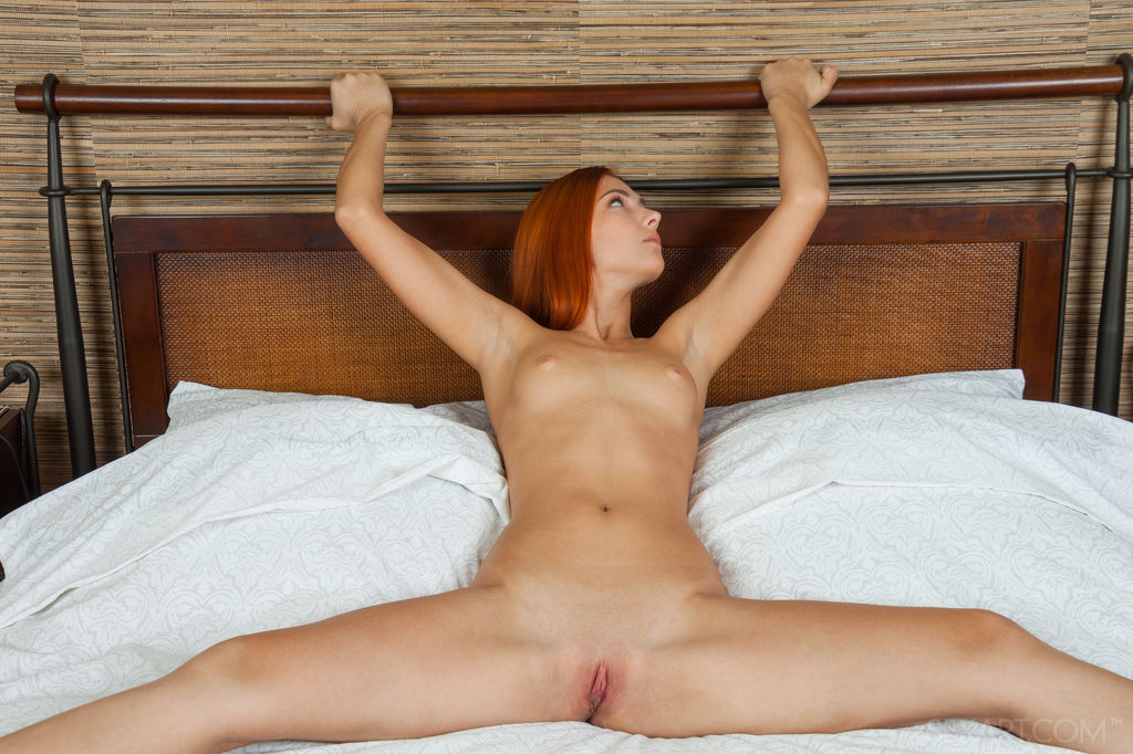 Sexy redhead Carinela with long and slender body lounging naked on top of the bed
