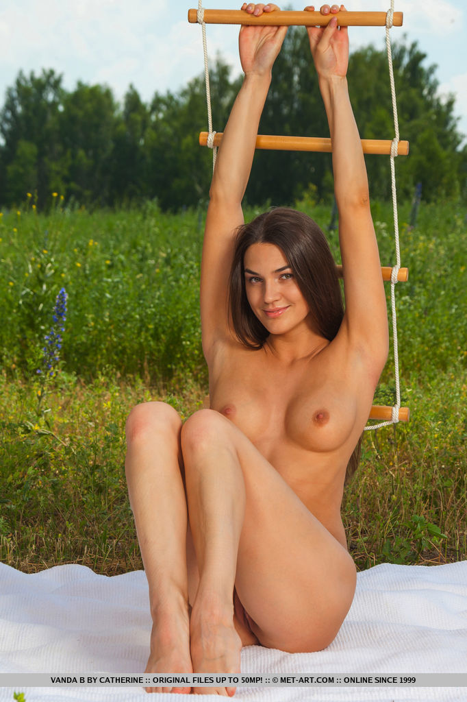 Vanda playfully poses naked with a rope ladder, showcasing her long and slender body