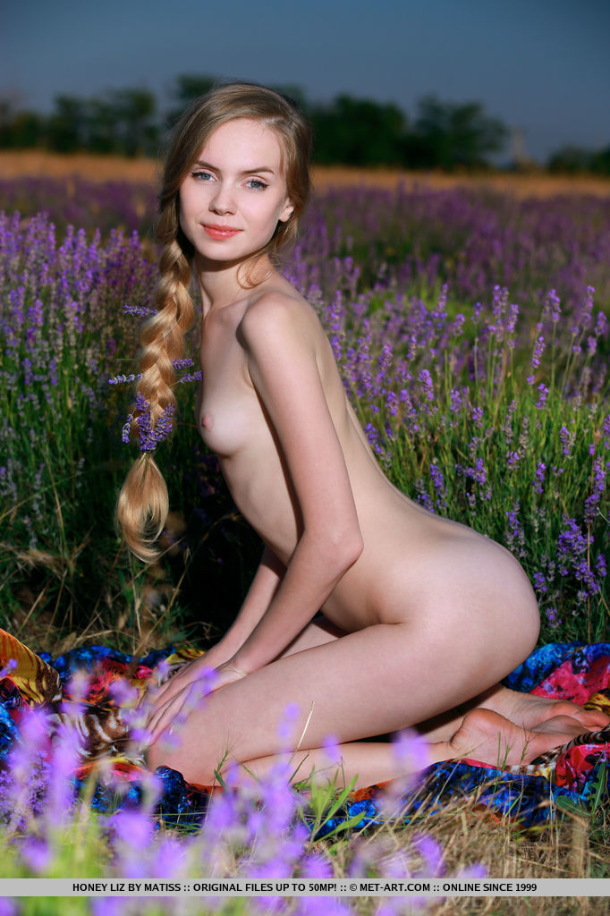 Youthful Honey Liz delightfully poses in the flowery field displaying her lean body   with creamy skin.