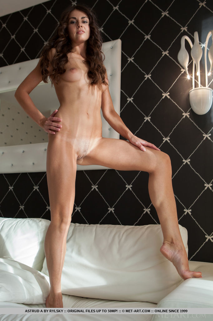 Blessed with an elegant beauty, Astrud A sits comfortably on top of the bed while showcasing her sexy, long legs, nice ass, and shaved snatch