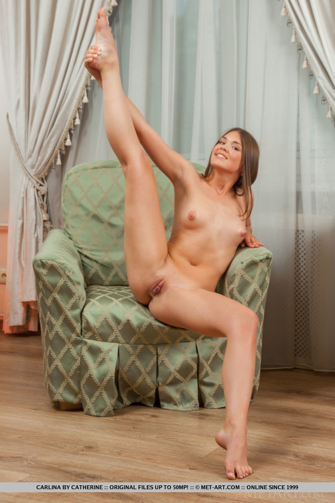 Carlina strisp her white top baring her slender body with round ass and meaty legs as she poses sensually on the sofa.