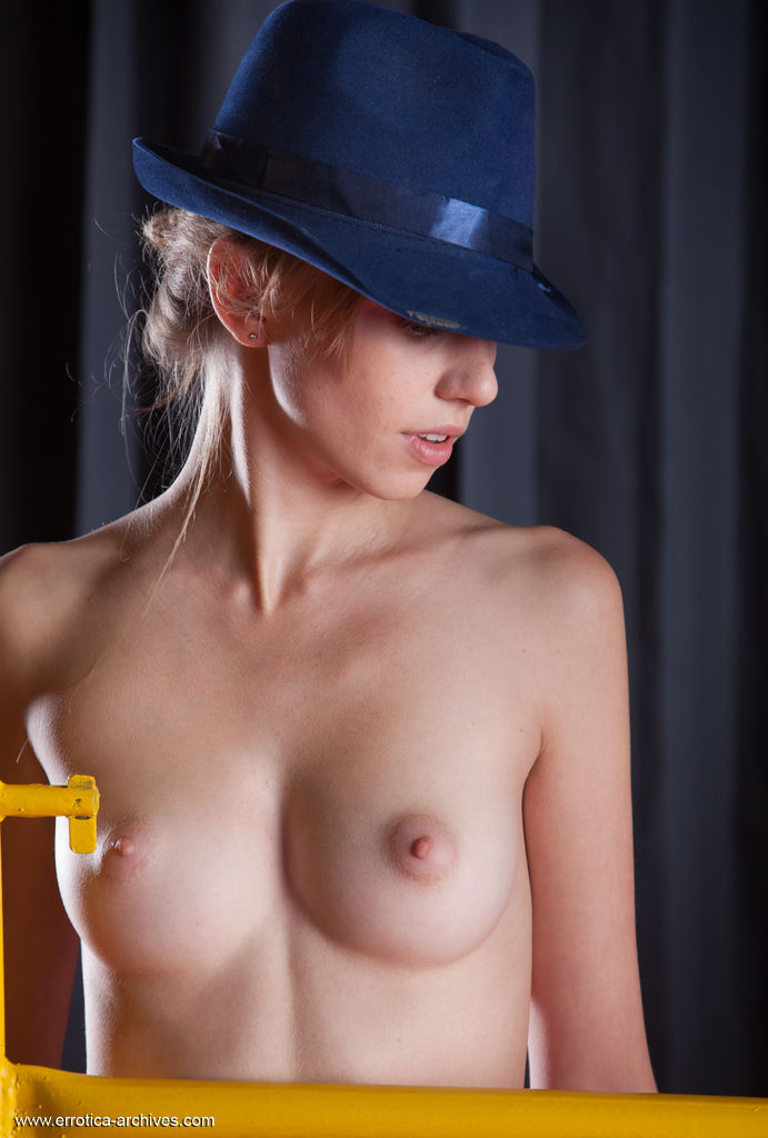 Katy D displays her naked, petite body and delectable assets as she poses in front of the camera with her fedora hat.