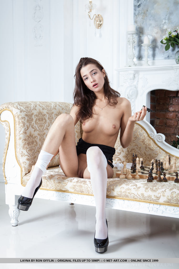 Layna posing sensually in black lace bodysuit, garter belt, white thigh-high stockings and stiletto shoes