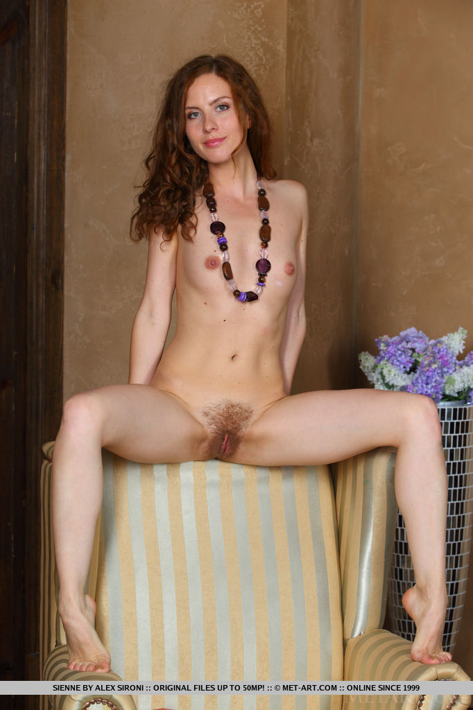 Redhead Sienne strips her white dress baring her lean, petite body and unshaven pussy as she poses on the couch.