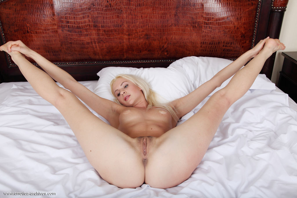 Sexy blonde Viviene bares her naked body as she spreads her legs and   poses sensually on the bed.