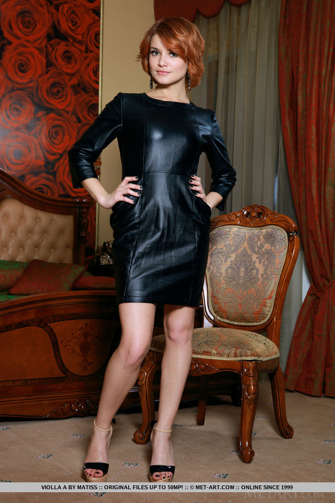 Sexy readhead Violla A in a black leather dress and matching high heels