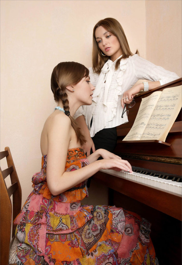 Two russian teens touch each other near piano