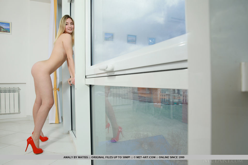 Amaly shows off her amazing body and meaty ass by the window.