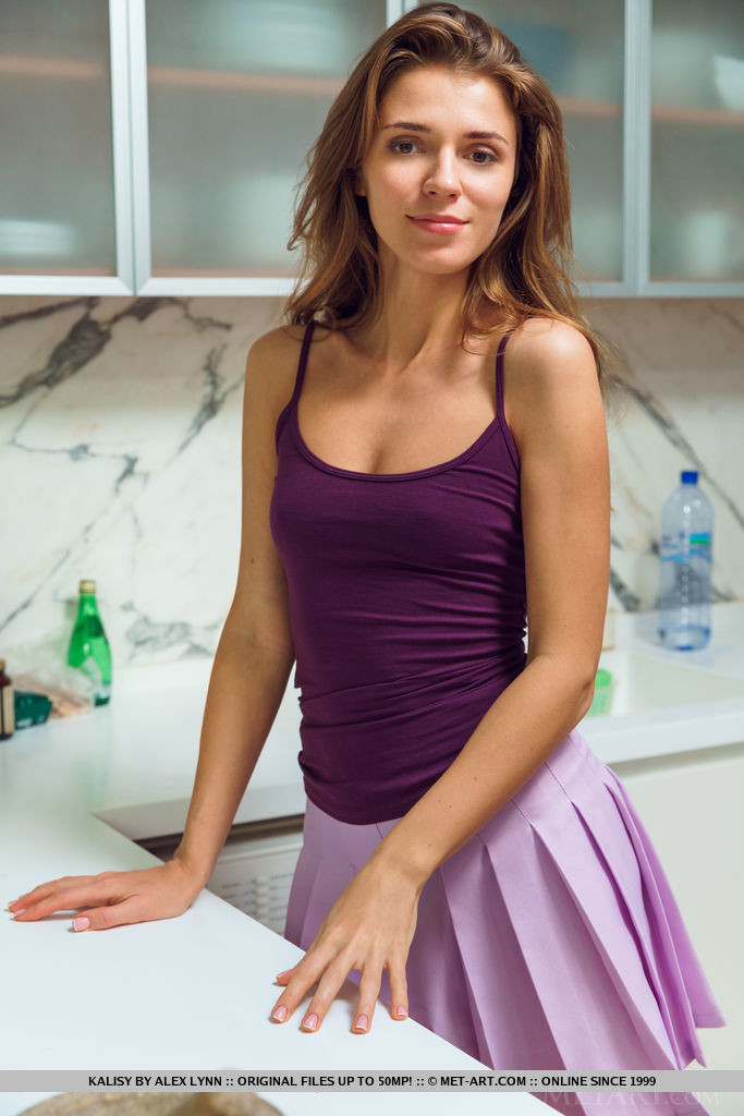 Kalisy strips her purple skirt baring her trimmed pussy in the kitchen.