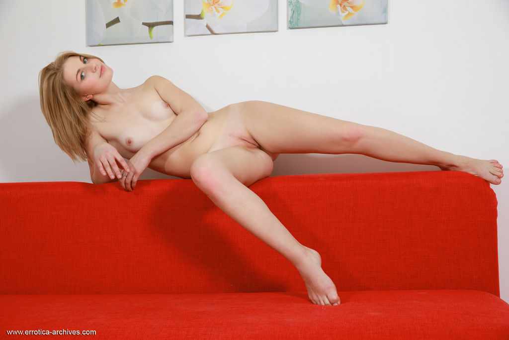 Margo Claire flaunts her smooth, creamy body and pink pussy on the red sofa.