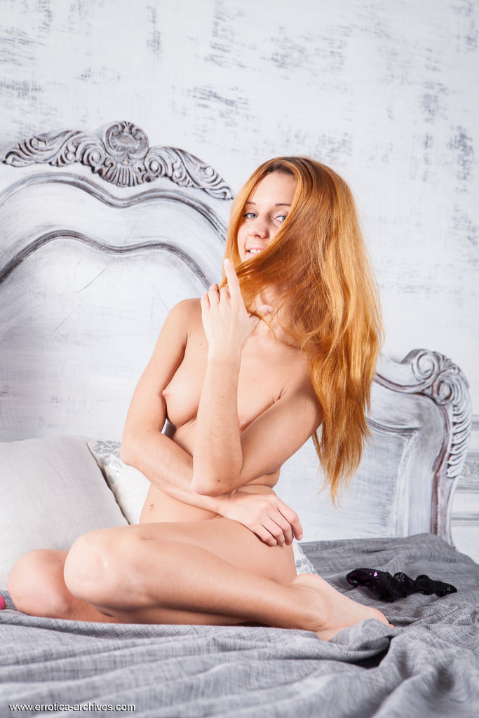 Redhead Roberta Berti strips on the bed as she displays her lusty body.