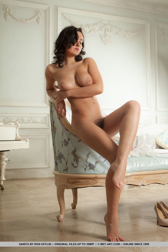 Sanita shows off her large tits and hairy pussy on the sofa.