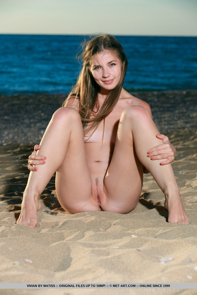 Vivian flaunts her nubile body and sweet pussy on the sandy shore.