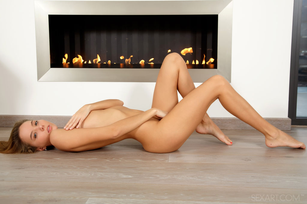 A charming Mango A strips naked and showcases her naked, petite body by the fireplace
